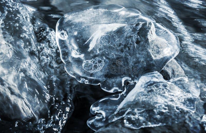Galleggianti veloci dell'acqua sulle pietre e sul ghiaccio immagini stock