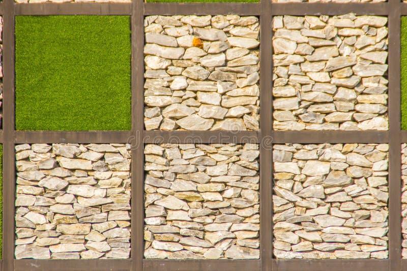 Fondo astratto della parete di pietra del ciottolo del fiume con la struttura dell'erba verde Inghiai la forma del fondo della pa immagini stock