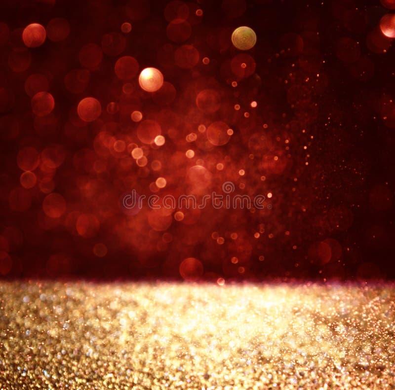 Fondo astratto delle luci del bokeh di scintillio dell'oro e di rosso, defocused immagini stock