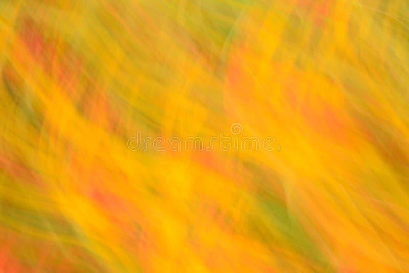 Fondo astratto nei toni gialli e rossi con effetto della sfuocatura fotografia stock