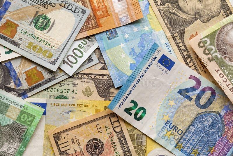 Fondo astratto variopinto delle banconote differenti , Fatture ucraine di valuta nazionale, dollari americani e euro Soldi e fotografie stock