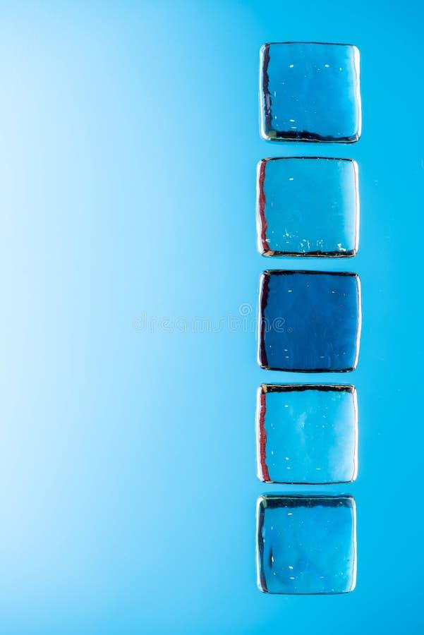 Fondo azul elegante con transparente hielo-como los cubos para las bebidas Foto macra puesta plano fotos de archivo libres de regalías