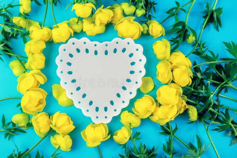 Fondo azul hermoso con un espacio en forma de corazón de la copia de una placa blanca con las flores amarillas del ranúnculo fotos de archivo