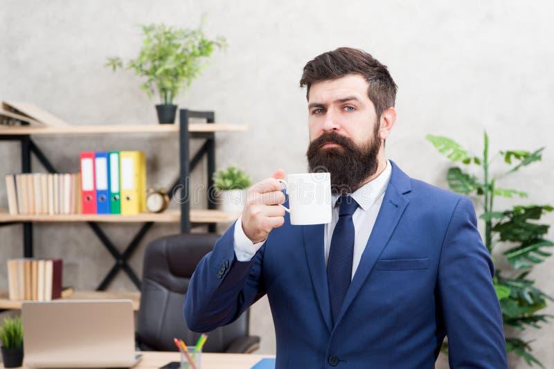 Fondo barbuto dell'ufficio del supporto della tazza di caffè della tenuta dell'uomo d'affari dell'uomo Rottura di rilassamento be immagine stock libera da diritti