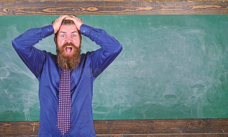 Fondo barbuto della lavagna della testa della tenuta dell'insegnante o dell'educatore dell'uomo Attenzione di paga al vostri comp fotografia stock libera da diritti