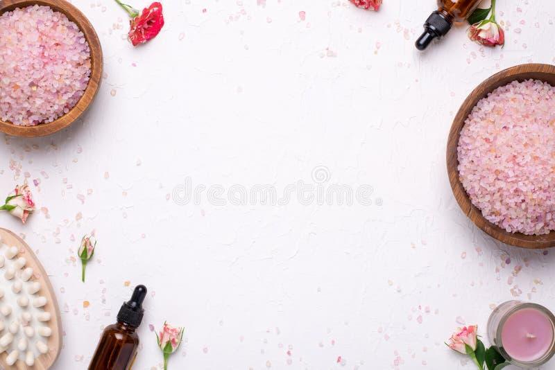 Fondo bianco con sale da bagno, il massaggiatore e le bottiglie di olio naturali fotografia stock libera da diritti