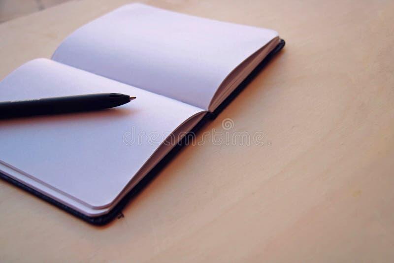 Fondo bianco con un taccuino e una penna fotografia stock
