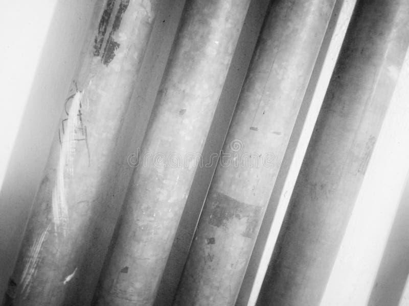 Fondo in bianco e nero e linee rette dei tubi d'acciaio fotografia stock