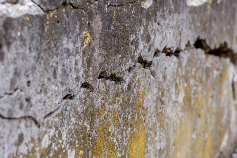 Fondo bianco incrinato di struttura della parete, parete molto vecchia con una crepa su  fotografia stock