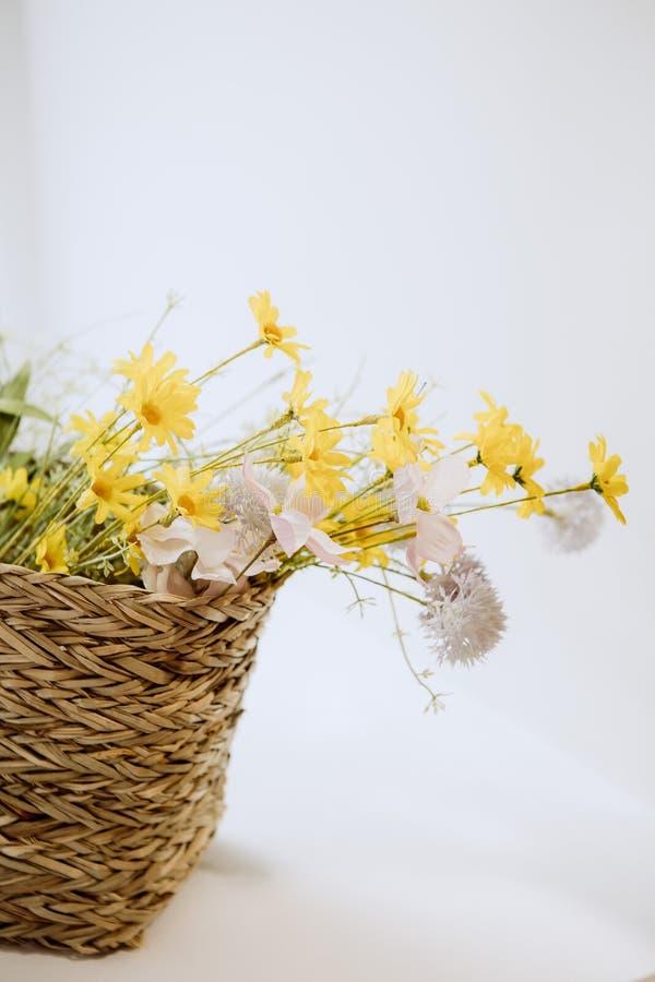 Fondo bianco rosa giallo dei fiori selvaggi del canestro immagine stock