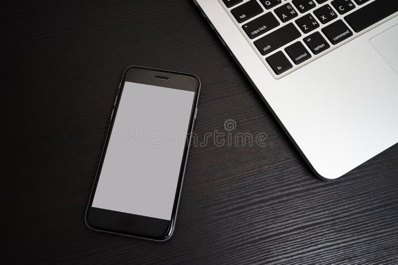 Fondo blanco del teléfono móvil con el teclado del ordenador portátil fotos de archivo libres de regalías