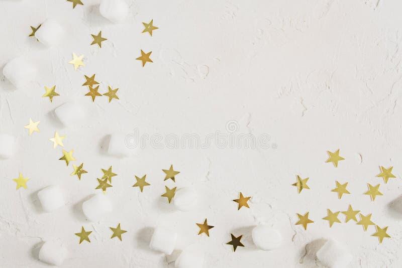Fondo blanco festivo con las mini melcochas y las estrellas de oro del confeti Tarjeta de felicitaci?n con el espacio de la copia fotografía de archivo