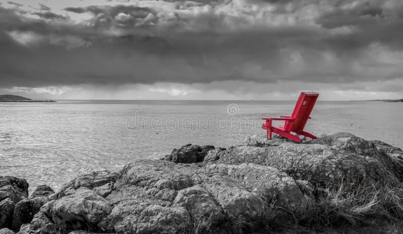 Fondo blanco y negro de la naturaleza de la silla roja foto de archivo