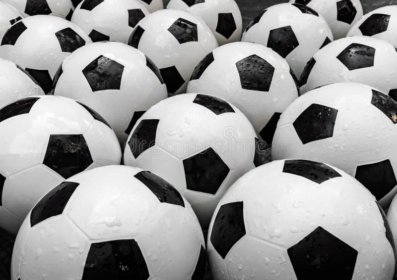 Fondo blanco y negro de muchos balones de fútbol Bolas del fútbol en un agua imagen de archivo libre de regalías