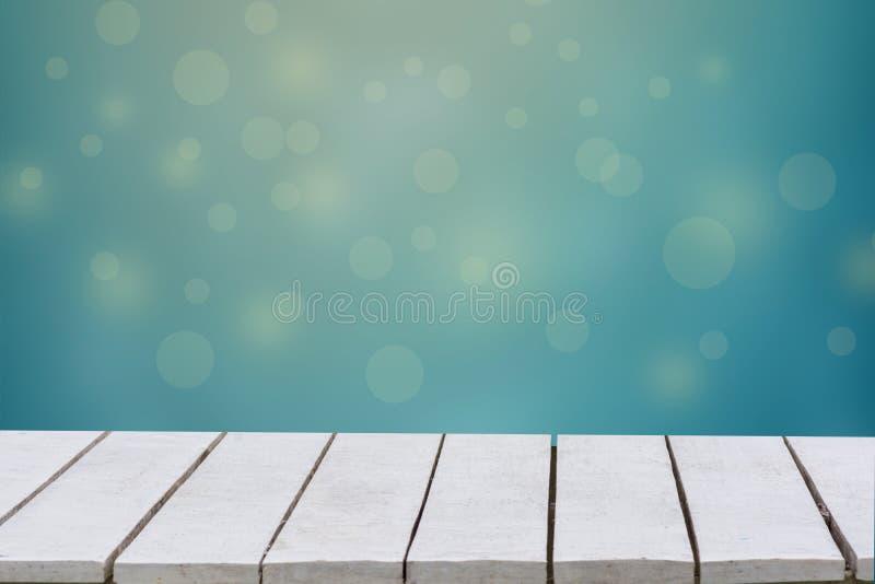 Fondo blu con il fuoco selettivo I precedenti verdi hanno una foglia e un'erba del bokeh su un pavimento di legno bianco Tavola v immagine stock libera da diritti