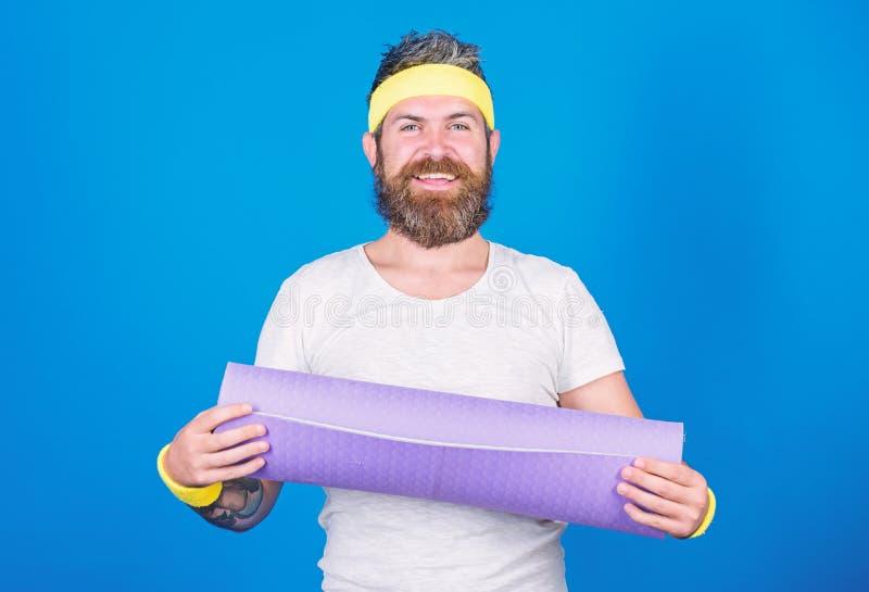 Fondo blu dell'atleta dell'uomo della tenuta della stuoia barbuta di forma fisica Lascia la classe di yoga di inizio Yoga come l' fotografia stock libera da diritti