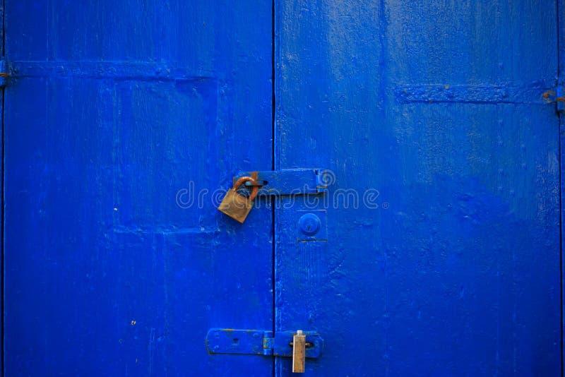 Fondo blu di legno della porta bloccato con due lucchetti arrugginiti Entrata invecchiata e chiusa, fine sulla vista con i dettag fotografie stock libere da diritti
