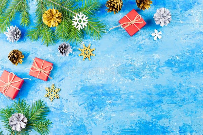 Fondo blu di Natale con i rami dell'abete, le decorazioni d'argento e dorate rosse dei giftboxes, spazio della copia fotografia stock