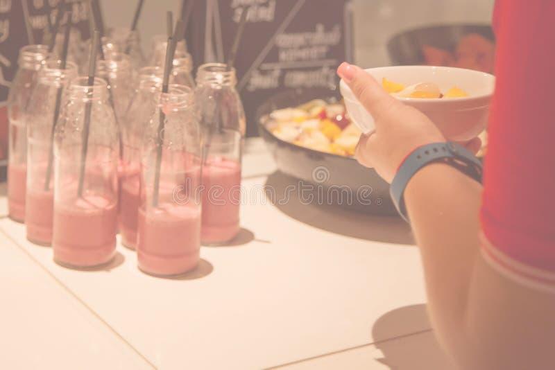 Fondo borroso con el sistema de los vidrios del smoothie y de la mano de la muchacha foto de archivo libre de regalías