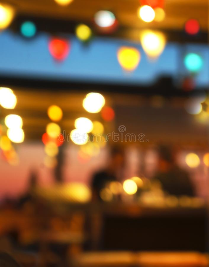Fondo borroso de la gente que se sienta en el restaurante, la barra o el club nocturno con el bokeh colorido de las luces fotografía de archivo libre de regalías