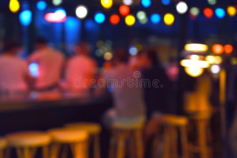 Fondo borroso de la gente que se sienta en el restaurante, la barra o el club nocturno con el bokeh colorido de las luces foto de archivo