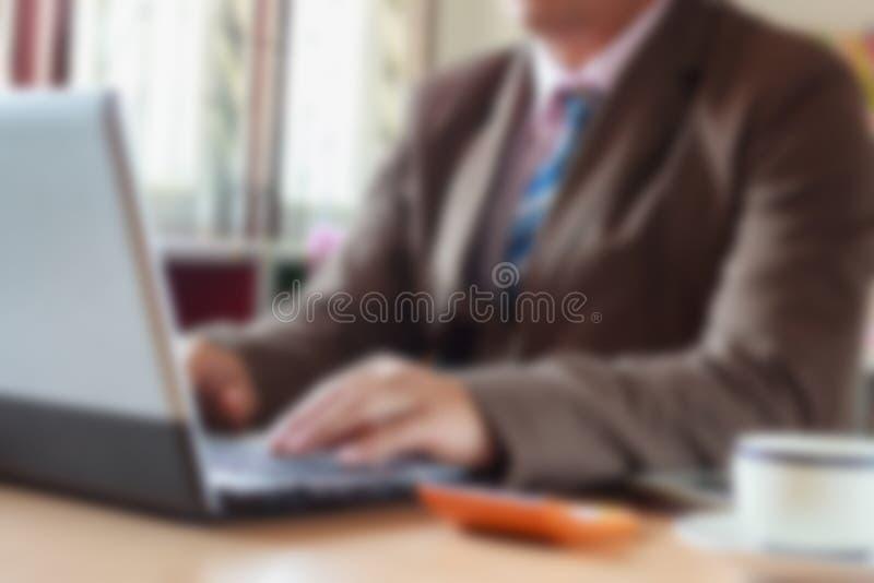 Fondo borroso de la oficina, oficinista en el ordenador foto de archivo