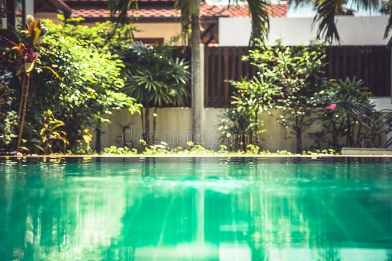 Fondo borroso de la piscina en el patio trasero del chalet tropical fotos de archivo