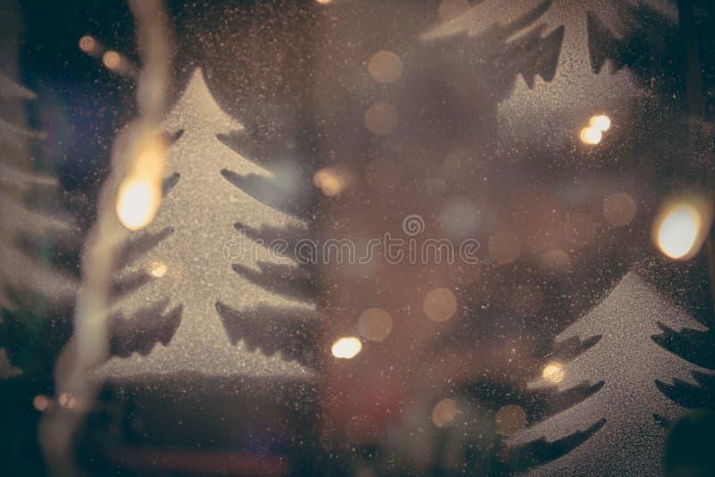 Fondo borroso entonado azul de los chrismas con los árboles de navidad y las luces de calle en estilo del vintage foto de archivo