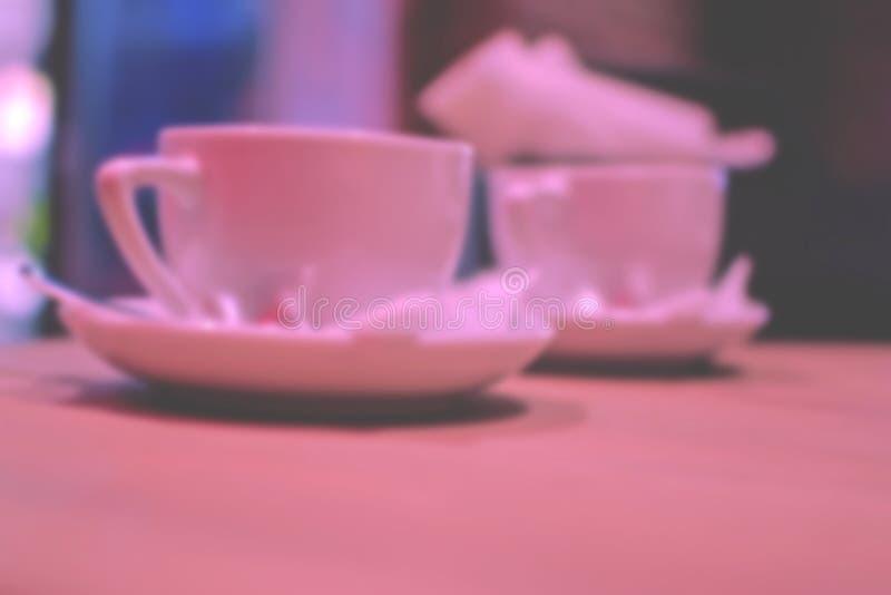 Fondo borroso: taza de café o de té en la tabla fotos de archivo