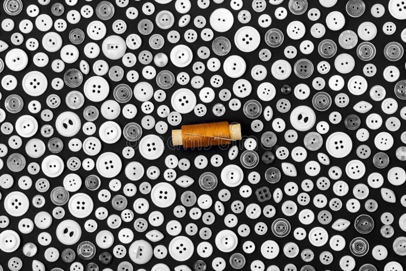 Fondo - botones ligeros en una superficie y un carrete oscuros del hilo amarillo con la aguja fotografía de archivo libre de regalías