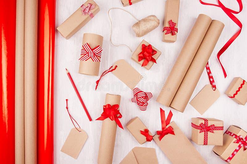 Fondo brillante de la Navidad - actuales cajas festivas con las cintas rojas, etiquetas, papel de rollos como modelo decorativo d imagenes de archivo