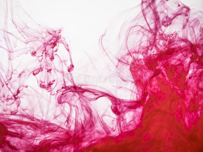 Fondo coloreado rojo abstracto La imagen del rojo congelado coloreó el flujo de pintura en agua Gotita de la pintura acrílica caí imagen de archivo