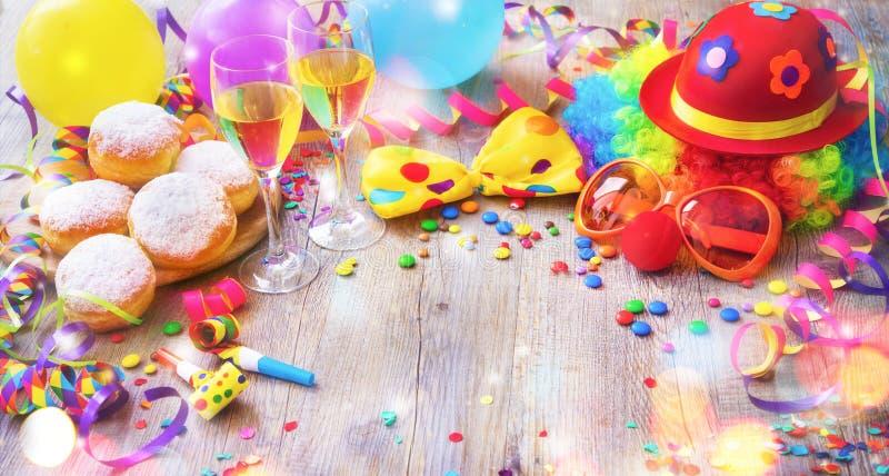 Fondo colorido del carnaval o del partido con los anillos de espuma, globos, flámulas y confeti y cara divertida fotos de archivo