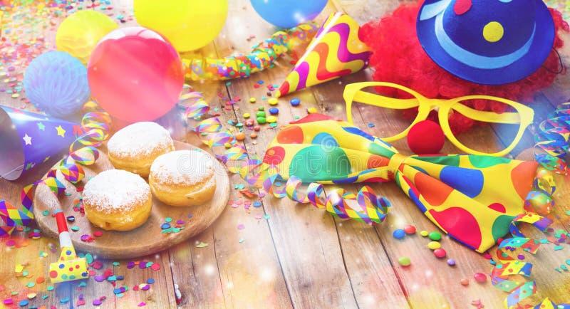 Fondo colorido del carnaval o del partido con los anillos de espuma, globos, flámulas y confeti y cara divertida fotografía de archivo