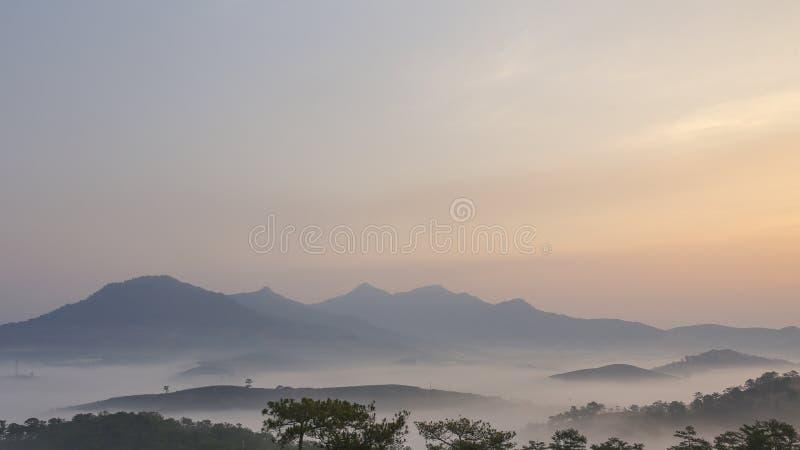 Fondo con aria fresca, luce magica e la foresta della copertura della nebbia densa nel plateau alla parte 2 di alba immagini stock