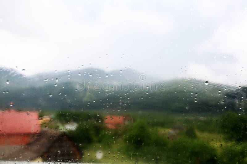 Fondo con descensos lluviosos en el vidrio de la ventana fotos de archivo