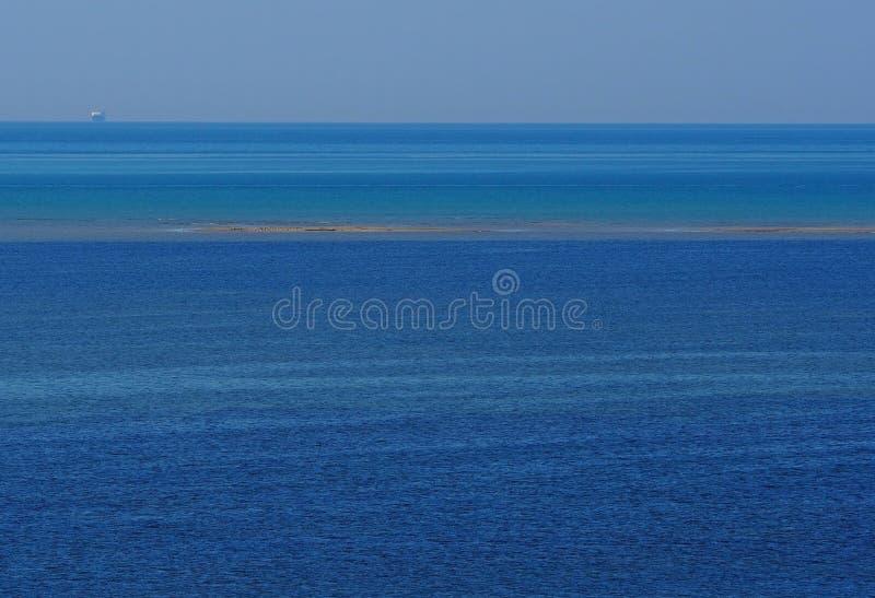 Fondo con diversas sombras del azul, una raya del paisaje marino de una pequeña isla arenosa emergida en la nave media y distante fotos de archivo
