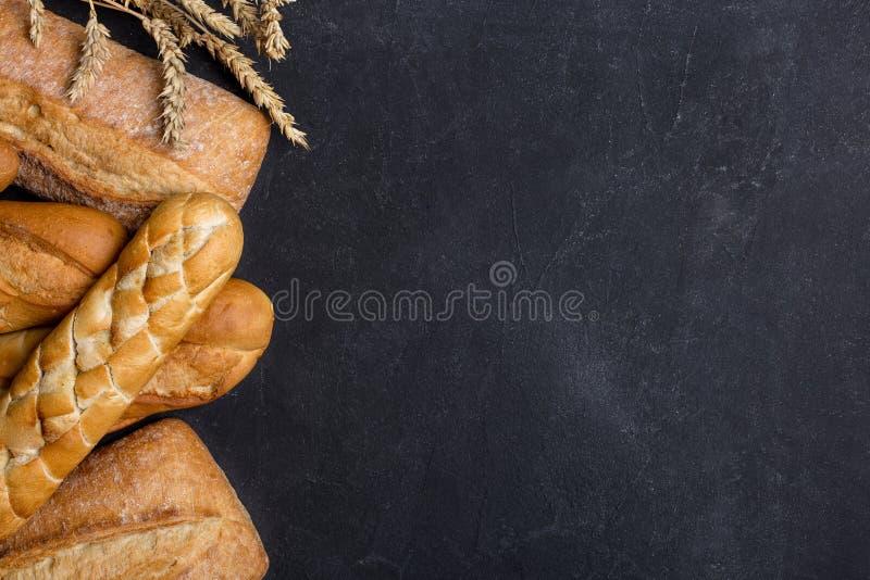 Fondo con el diferente tipo de pan en fondo oscuro Borde izquierdo fotos de archivo libres de regalías