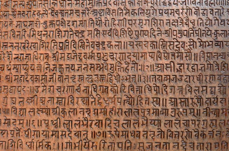 Fondo con el texto sánscrito antiguo grabado al agua fuerte en una tableta de piedra imagenes de archivo