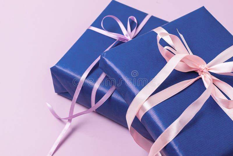 Fondo con las cajas de regalo en papel de embalaje azul con las cintas que mienten en presentes planos horizontales del rosa del  foto de archivo