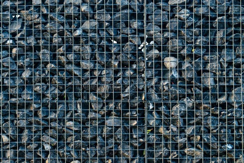 Fondo con las piedras machacadas, elementos, grava en una rejilla del metal imagenes de archivo