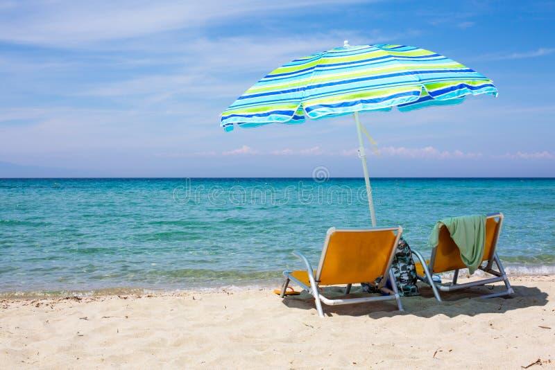 Fondo con las sillas de playa y paraguas colorido en la playa arenosa foto de archivo