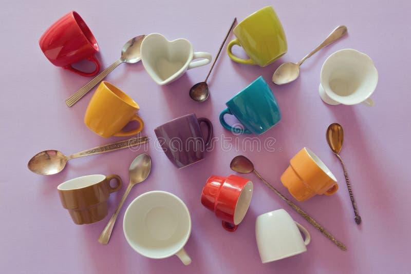 Fondo con las tazas y las cucharas vacías coloridas de café Visión desde arriba foto de archivo libre de regalías