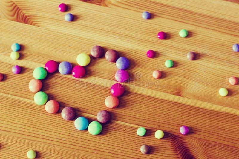 Fondo con los caramelos del color en la forma de un corazón en la tabla de madera en el tono del vintage foto de archivo libre de regalías