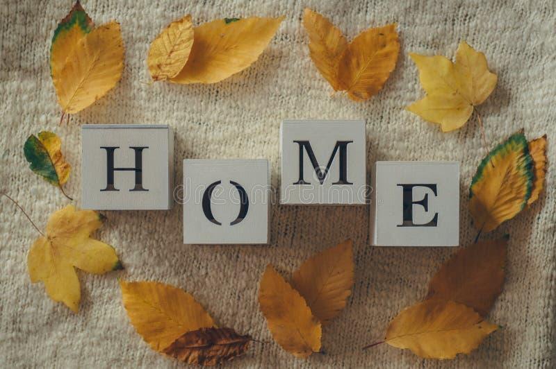 Fondo con los suéteres calientes y el HOGAR de la inscripción Pila de ropa hecha punto con las hojas de otoño, géneros de punto,  foto de archivo
