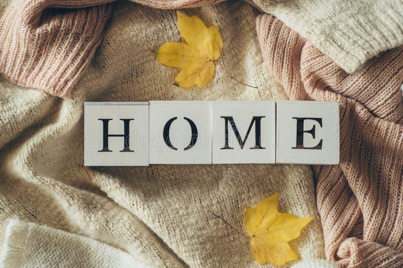 Fondo con los suéteres calientes y el HOGAR de la inscripción Pila de ropa hecha punto con las hojas de otoño, géneros de punto,  imagen de archivo