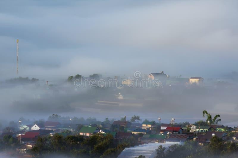 Fondo con nebbia densa e luce magica all'alba L'azienda agricola e le casette del caffè in sole brillante fotografie stock