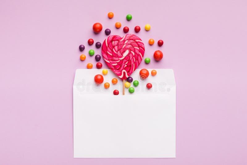 Fondo concettuale di amore, lecca-lecca a forma di del cuore in busta fotografia stock
