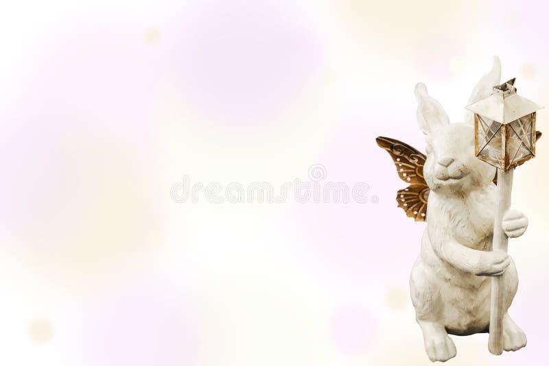 Fondo - coniglietto bianco con le ali e la decorazione della lanterna isolata sul pannello pastello - Pasqua o primavera immagine stock libera da diritti