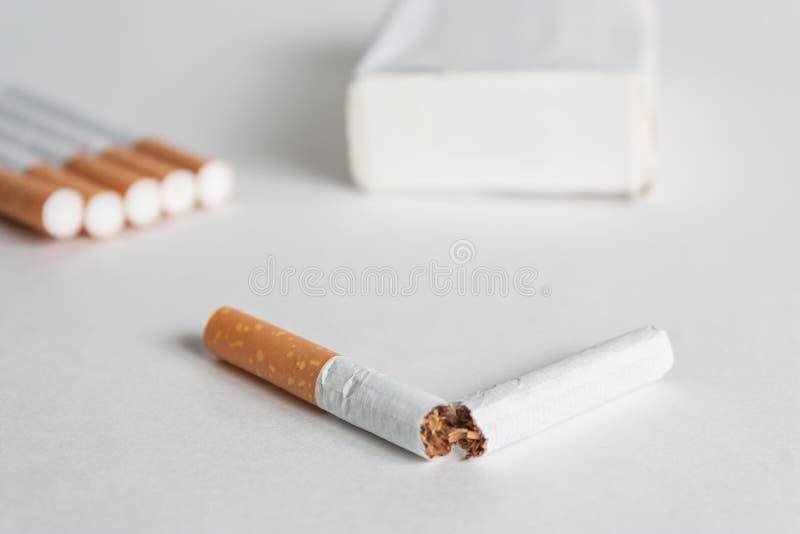 Fondo contro il fumo con la sigaretta rotta immagine stock